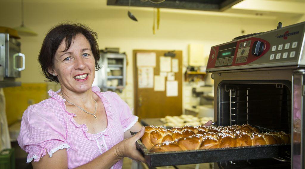 Frau zieht frisch gebackene Milchteig-Strirzel aus dem Ofen