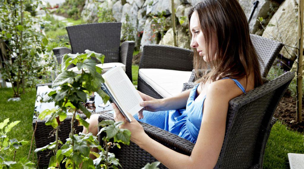 Frau in blauem Sommerkleid beim Lesen in einem Rattansessel im Garten