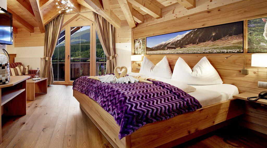 Hotelzimmer mit Einrichtung aus Naturholz, lila Bettüberwurf