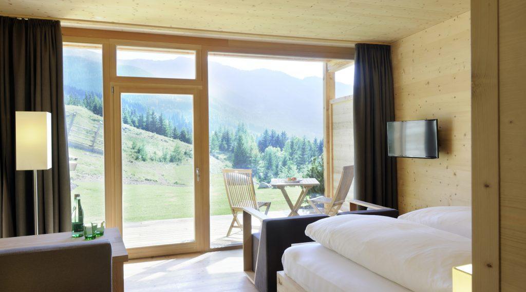 Blick aus dem Fenster des Hotelzimmer auf eine Almwiese