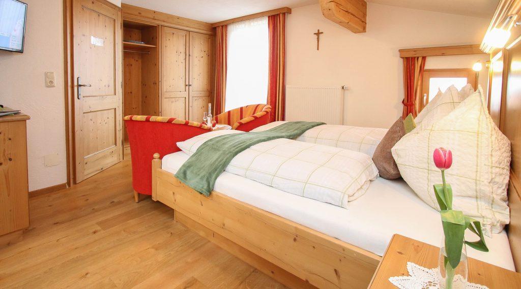 Hotelzimmer mit Doppelbett, roten Sesseln und einer rosa Tiulpe am Nachttisch