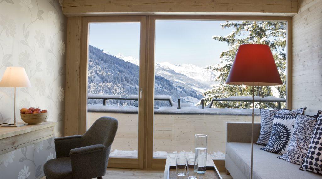 Blick aus dem Hotelzimmer auf das verschneite Gasteinertal, rote Stehlampe und helle Couch im Zimmer
