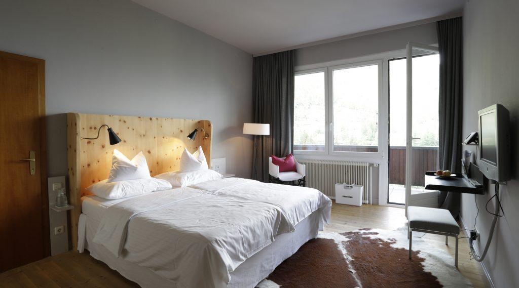 Hotelzimmer mit weiß überzogenem Bett und Kuhfell als Teppich