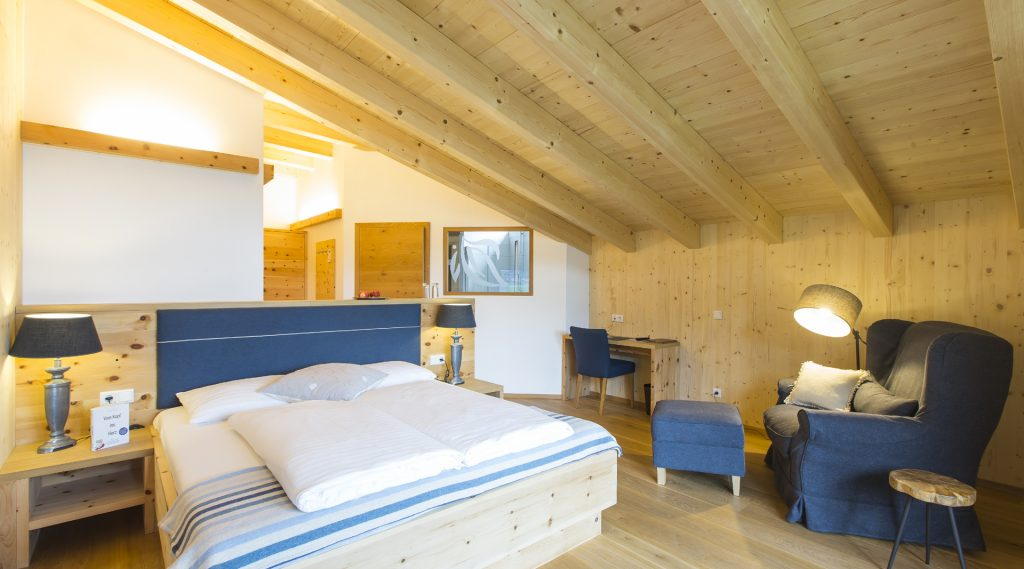 Mansadenzimmer mit blau-weißem bettüberwurf und blauen Sesseln, Decke und Tram aus Holz
