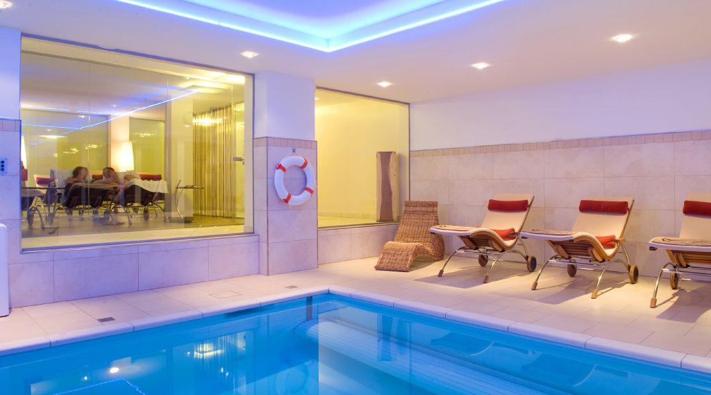Hallenbad mirt blauer Wasserfläche und Liegen mit roten Pölstern