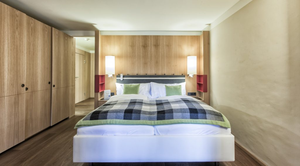 Einfach, aber edel eingerichtetes Doppelzimer mit kariertem Bettüberwurf