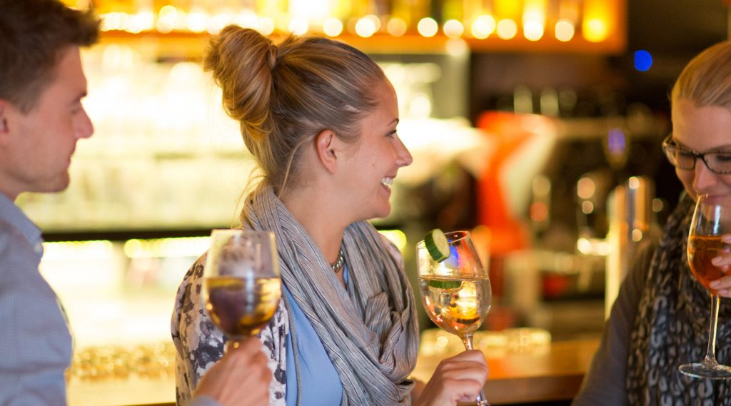Drei junge Leute stehen mit einem Glas Wein in der Hand an der Bar