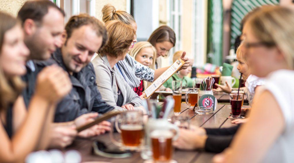 Menschen an einem langen Tisch im Gasthaus