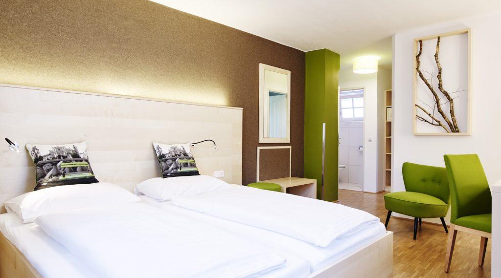 Doppelzimmer - weiß überzogenes bett, grüne Sitzmpbel