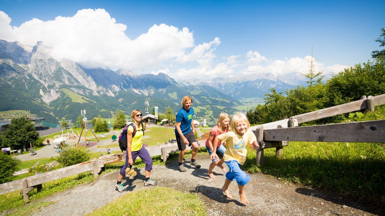 Eltern und zwei kinder wandern auf die Alm und haben dabei großen Spaß