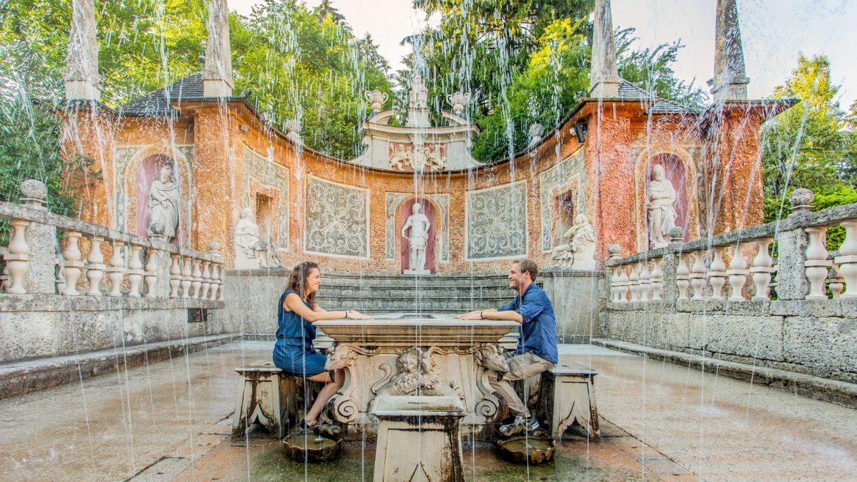 Ein Pärchen sitzt einander am steinernen Tisch der Wasserspiele Hellbrunn gegenüber und lächelt sich zu.
