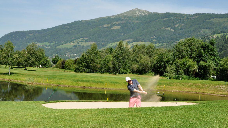Golfer schlägt den Ball aus dem Snadbunker.
