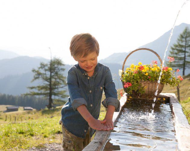 Junge am Wassertrog