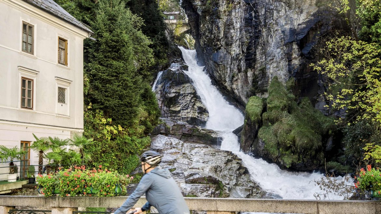 Radfahrer vor dem tosenden Wasserfall in Bad Gastein