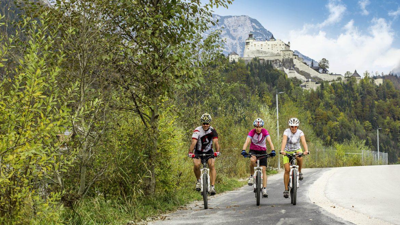 Drei Radfahrer fahren auf dem Tauernradweg mit Burg Hohenwerfen im Hintergrund