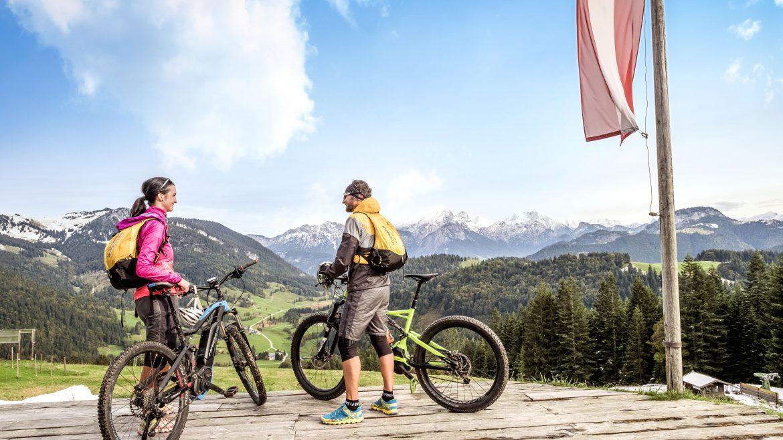 Zwei E-Mountainbiker genießen die Aussicht auf die umliegenden Berge