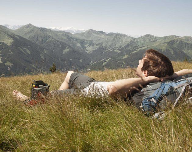 Mann entspannt auf Wanderung im Gras