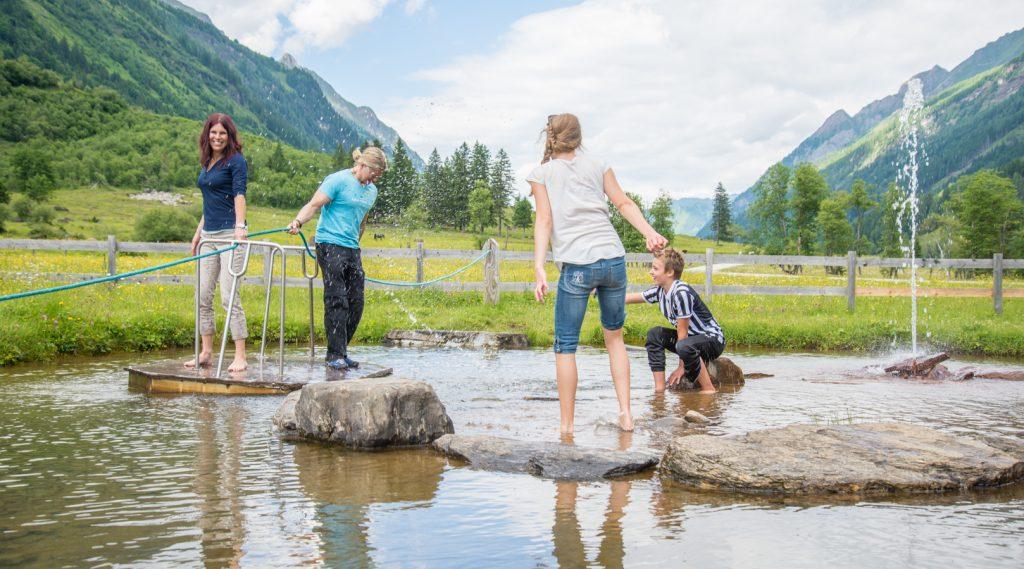 Familie plantscht im Wasser im Käfertal.