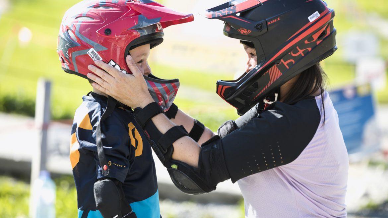 Erwachsener hilft Kind beim Aufsetzen des Bikehelms