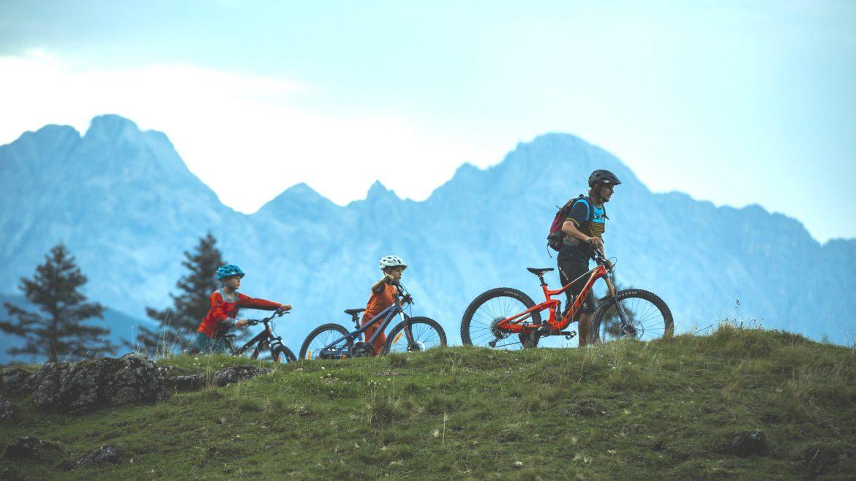 Familie mit dem Mountainbike im Gegenlicht, im Hintergrund Bergkulisse