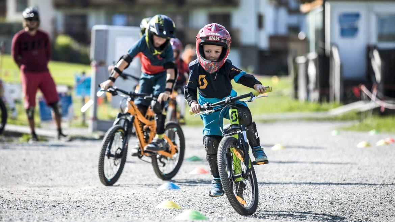 Kinder mit Helm am Mountainbike im Bikepark