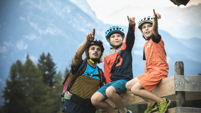 Vater mit zwei Jungs mit Radhelmen, Pause vom Biken
