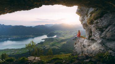 einsame Wanderin genießt Blick auf den See und die Berge