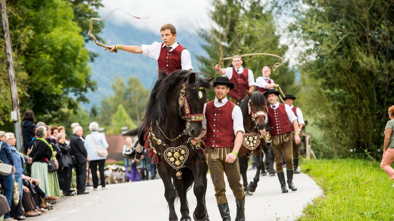 Eine Schnalzergruppe sitzt auf stolzen Pferden und trabt an einigen Zusehern vorbei.