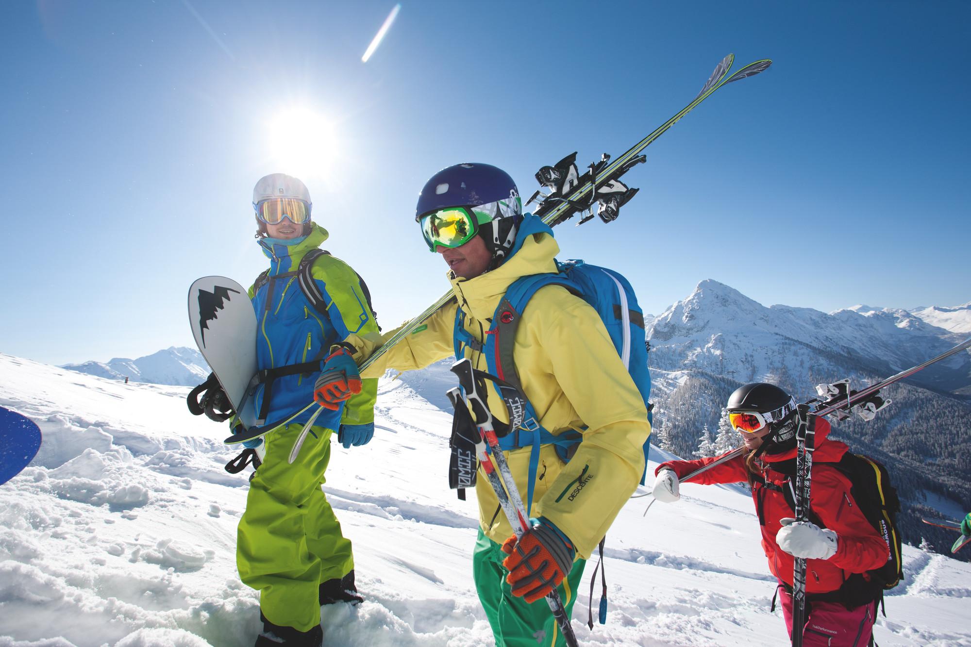 Drei Freerider, davon zwei Skifahrer und ein Snowboarder, steigen gemeinsam zum Freeriden auf
