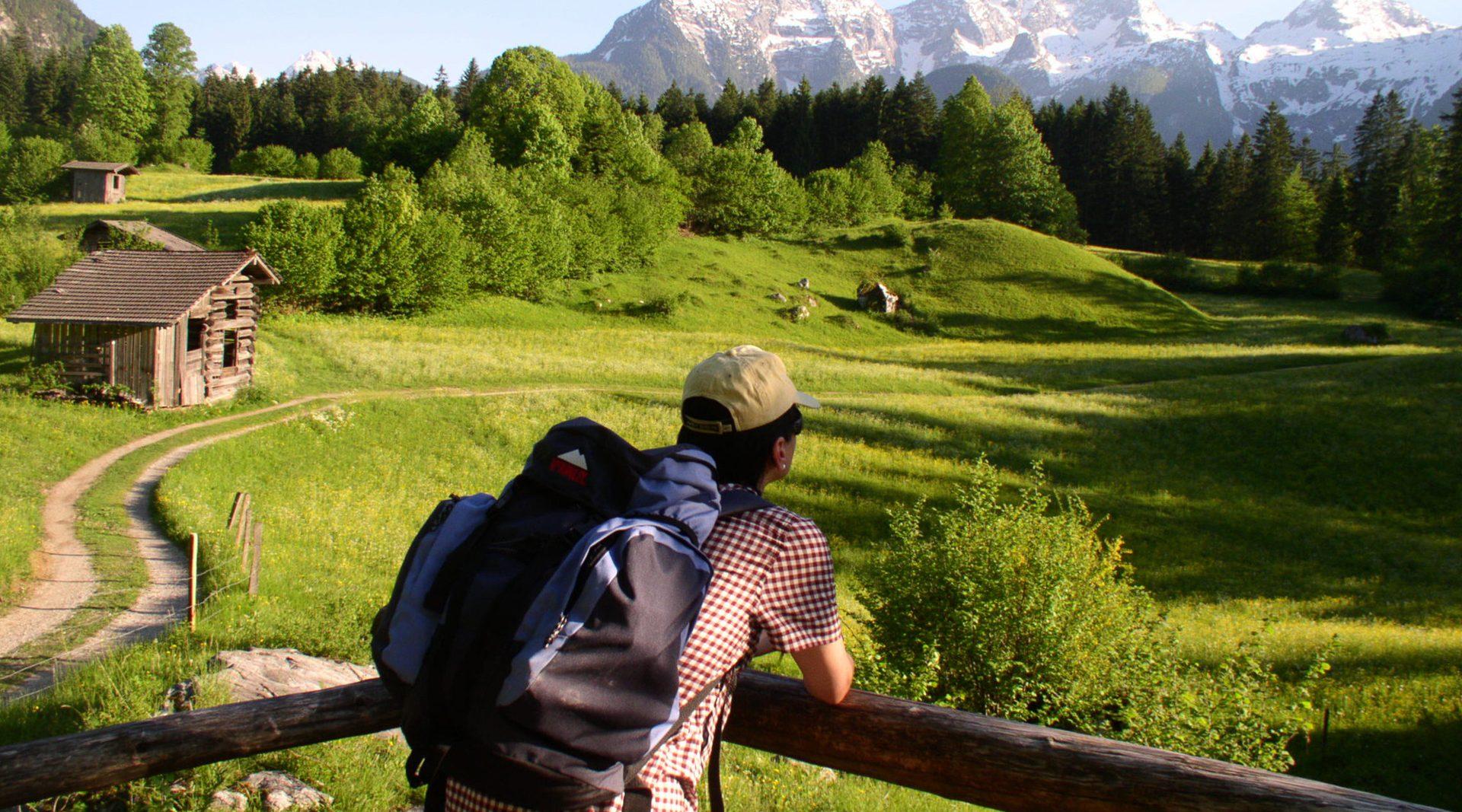 Ein Pilgerer mit Rucksack blickt über die Almwiese in die Ferne