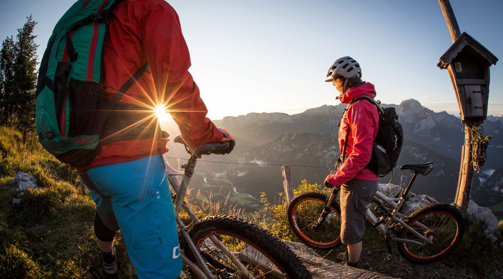 two mountain bikers enjoying their peak victory