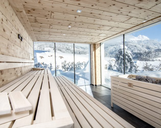 Empty stone pine sauna with a great view into the snowy winter landscape