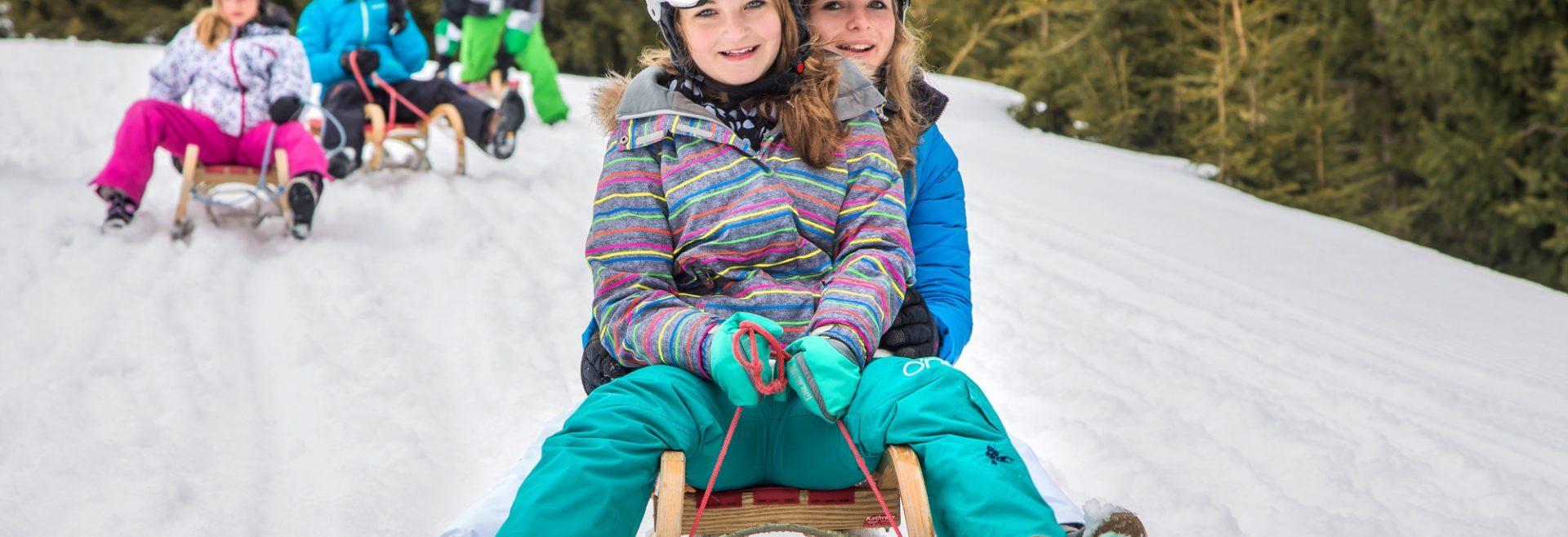 Kinder auf ihren Rodeln im Schnee