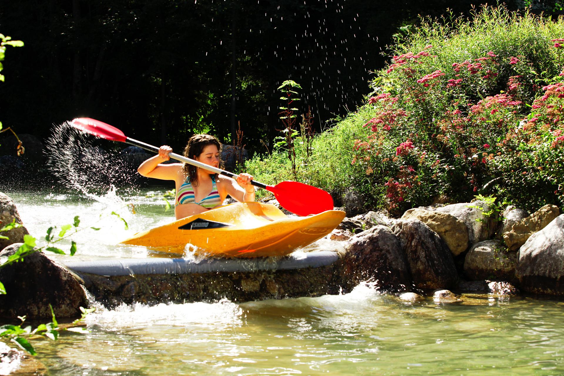 Junge Frau im gelben Kanu mit rotem Paddel