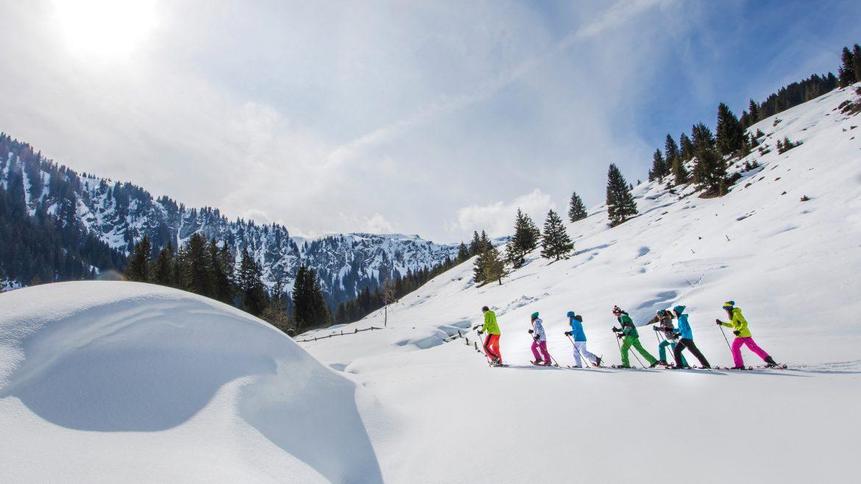 Schneeschuhwanderer gehen hintereinander durch den Tiefschnee.