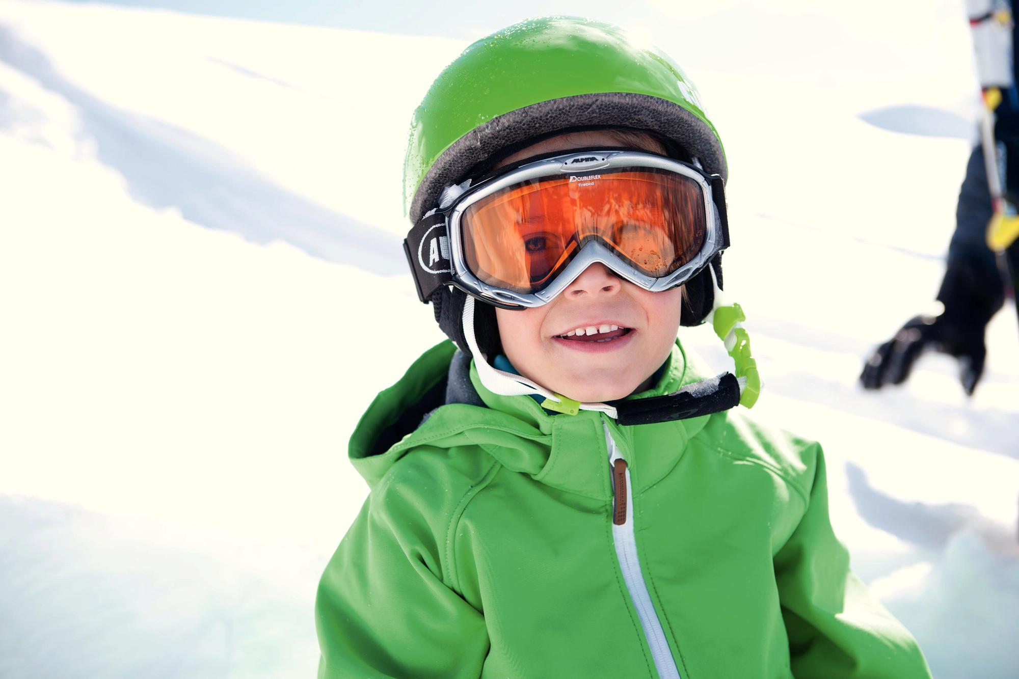 Bub mit grüner Jacke und grünem Helm hat sichtlich Spaß am Skifahren