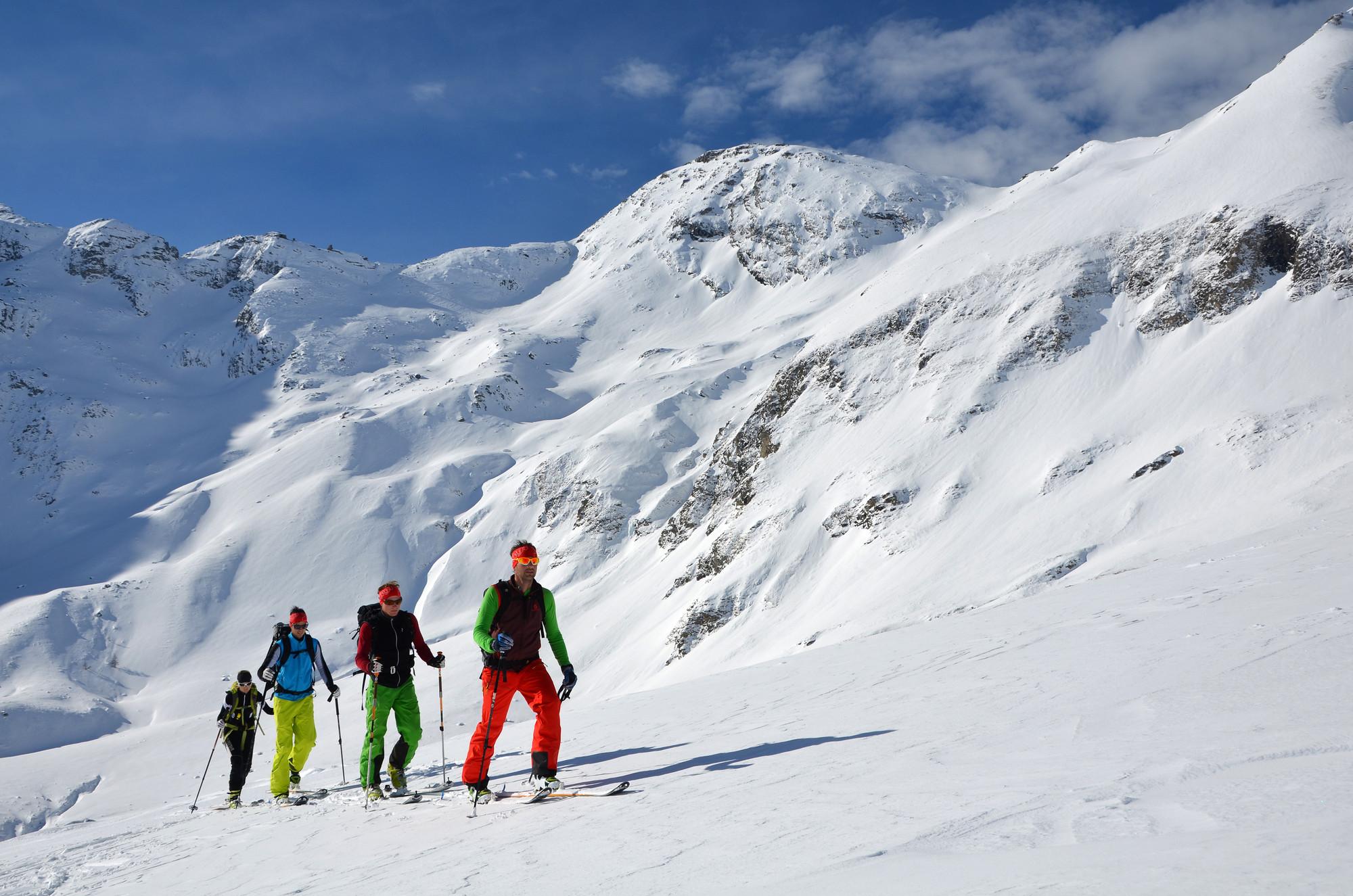 Vier Skitourengeher steigen langsam dem Gipfel entgegen.