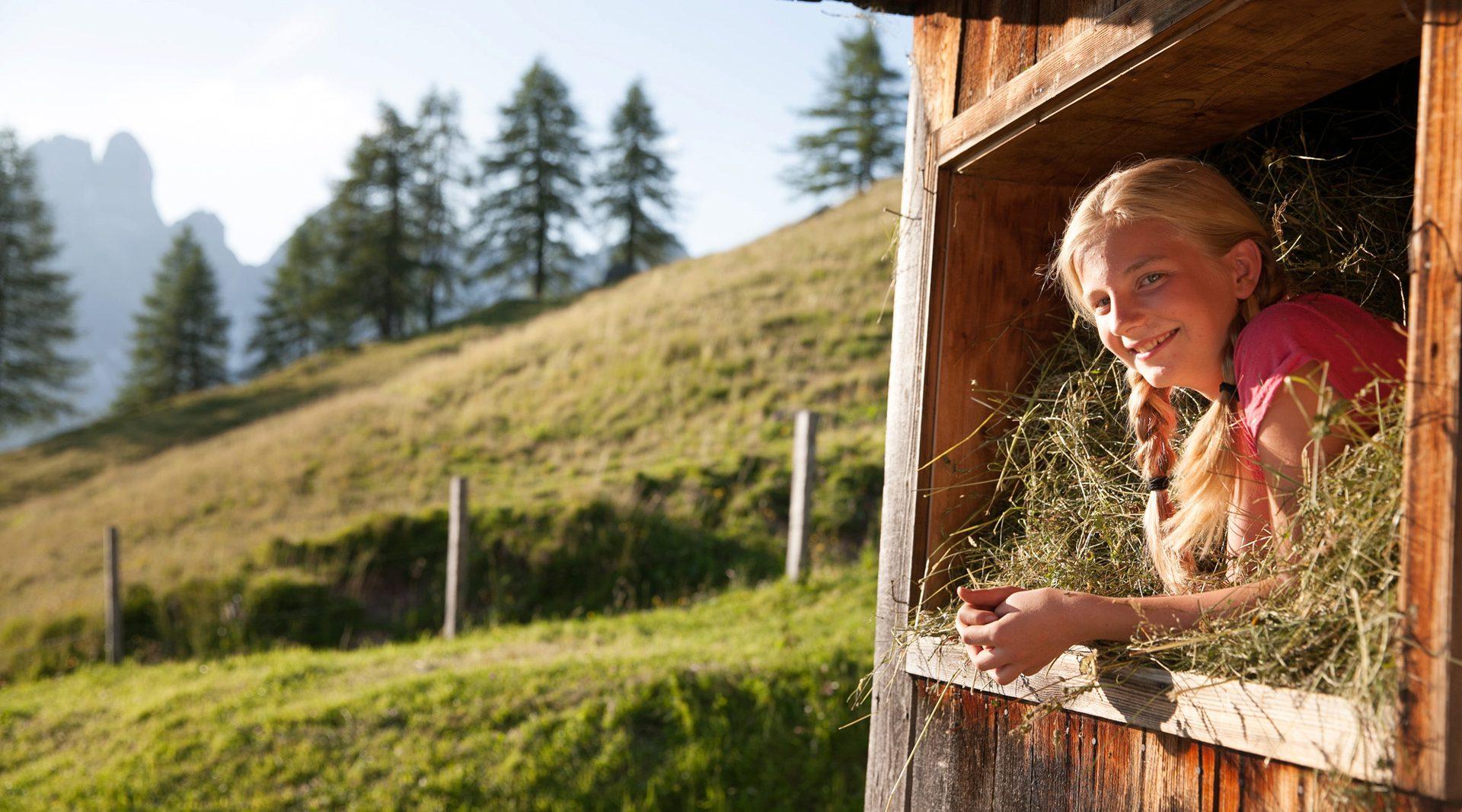 Frau sitzt im Heu am Bauernhof