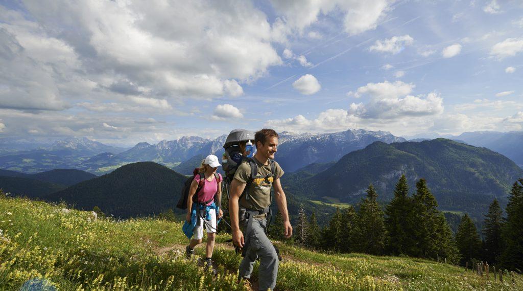 Mutter und Vater mit Kind in der Rückentrage auf einer Almwiese