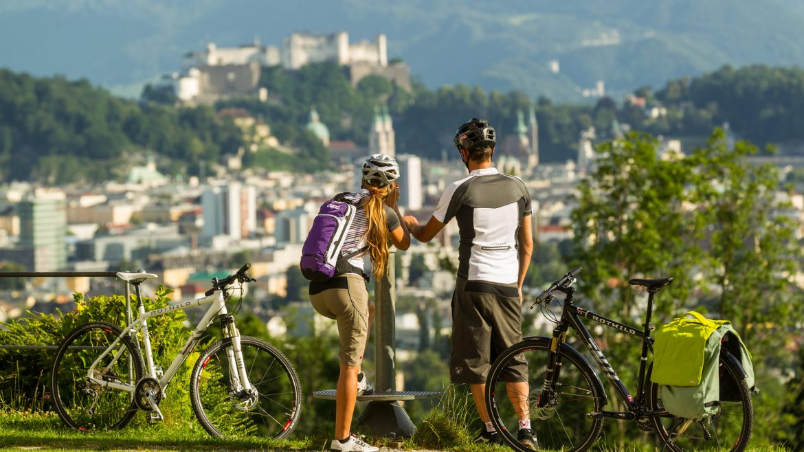 A biking couple with view over Salzburg