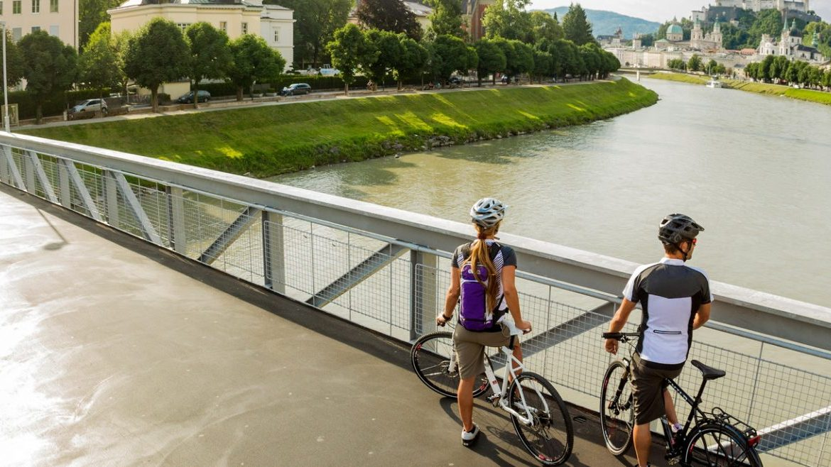 ©SalzburgerLand Tourismus - short break with beautiful view, 2 cyclists on bridge over Salzach - Tauern cycle path