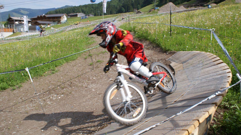 Kleiner Bike-Profi in voller Montur inklusive Helm auf der Downhill-Strecke