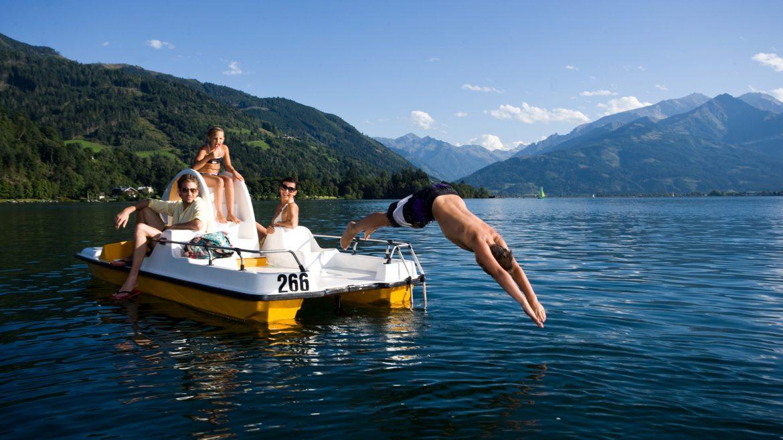 Familie am gelben Tretboot - Kind köpfelt ins Wasser