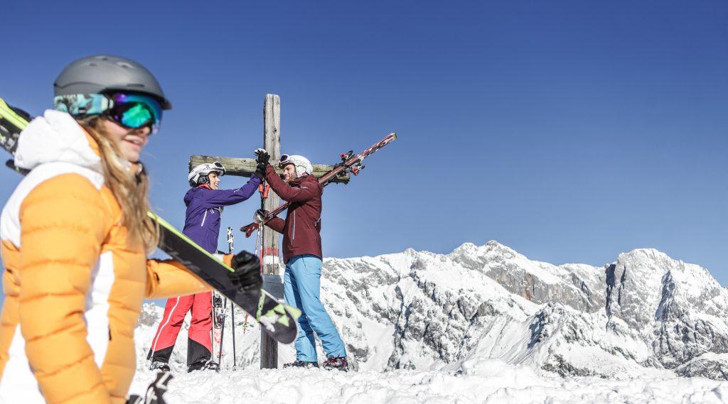 Familie mit Skiern am Gipfelkreuz.