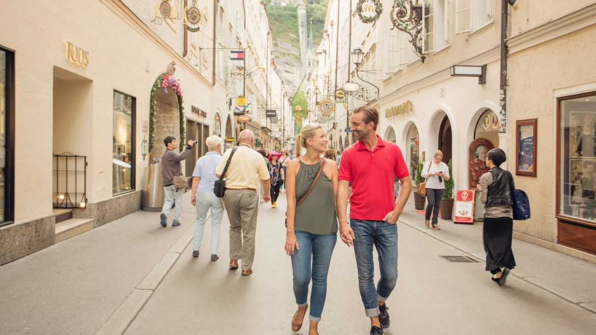 a group of people walking down a street in Salzburg