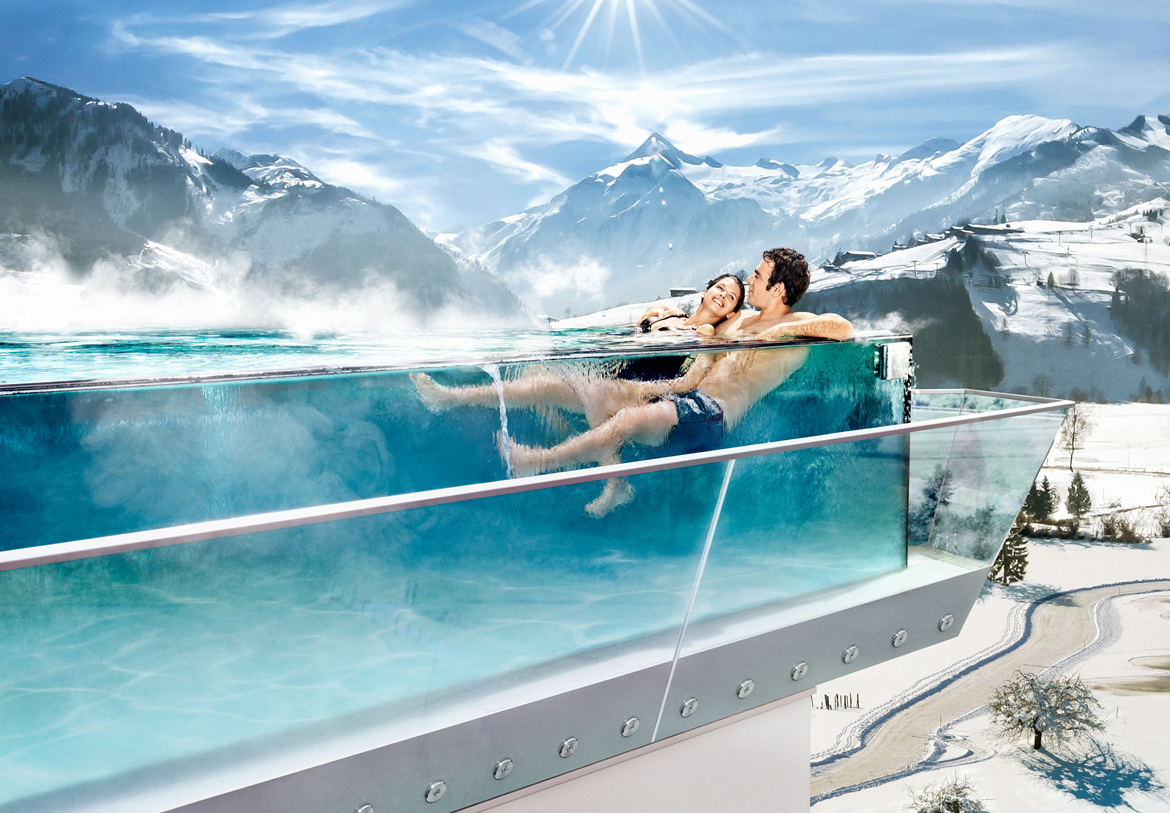 A couple relaxes in the skyline pool of the Tauern Spa Zell am See-Kaprun