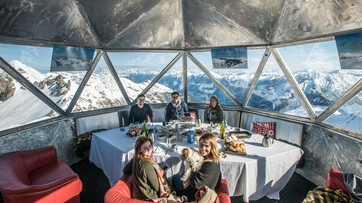 a group of people eating on a metal building with snowy mountain in the background