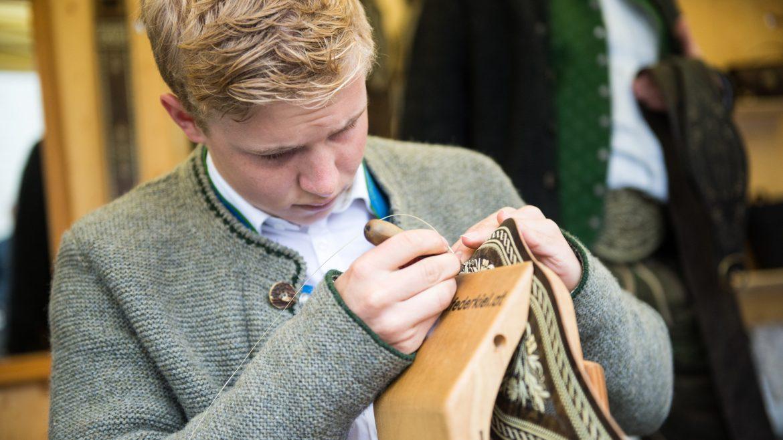 fiatal szőke fiú halványszürke, népviseleti kötött kabátban, Federkielstickerei hímzés közben