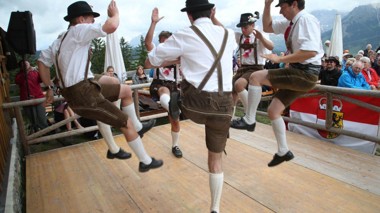 deszkaszínpadon bőrnadrágos, fehér inges, kalapos férfiak járják az ugrálós Schuhplatteln táncot