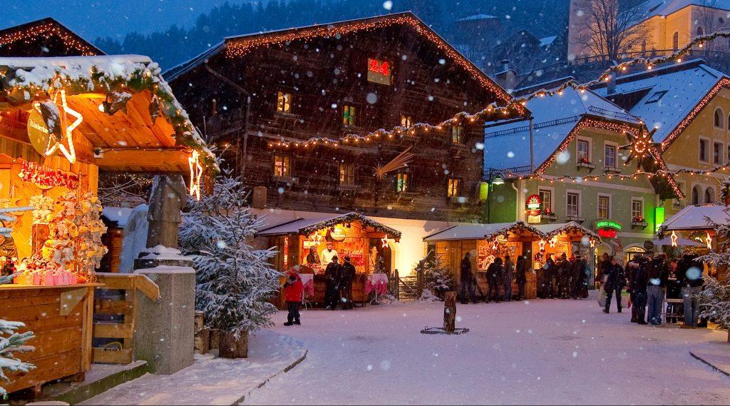 Mercatino di Natale in piazza a Grossarl mentre nevica